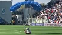 Cilvēks ar izpletni nolaižas futbola spēlē